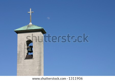 A church bell tower against a clear blue sky with the moon in the background. Landscape aspect with copy space. - stock photo