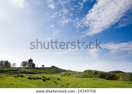 A church on a hill and a green meadow