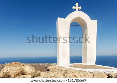 A church with a blue dome overlooks the spectacular caldera surrounding the beautiful island, Greece - stock photo