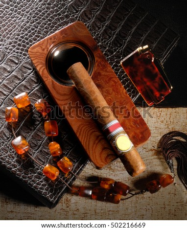a cigar in a old style vintage composition with a lighter from amber and a rosary in pan