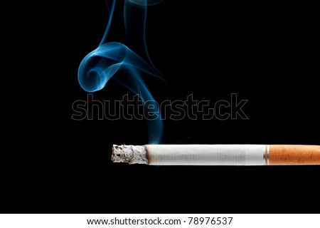 A cigarette burning isolated on a black background - stock photo