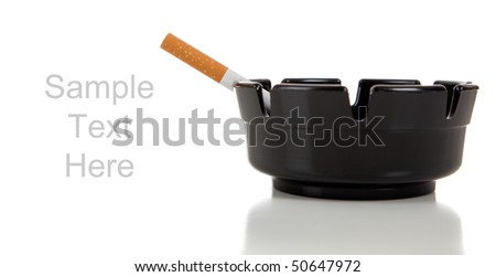 A cigarette in a black ashtray on a white background with copy space - stock photo