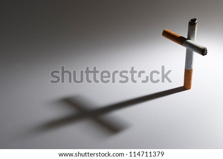 A cigarette with it shadow making a cross - stock photo