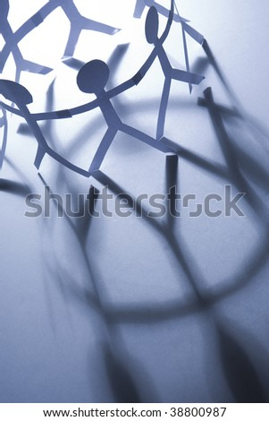 A circle of paper figures with long shadows - stock photo
