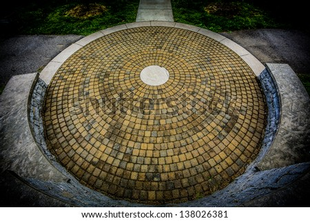 A circular stone floor with a round stone center piece surrounded by a raised stone wall and a concrete walking path - stock photo