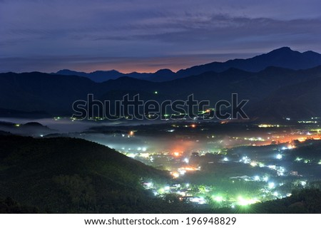 A city at night looking down from the mountains. - stock photo