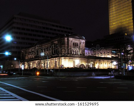 A city building on the corner of a well lit street at night. - stock photo