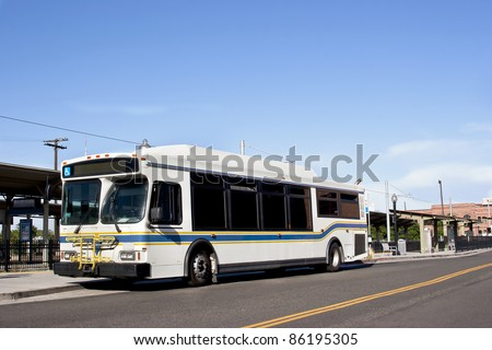 A city bus stops in a downtown district. - stock photo