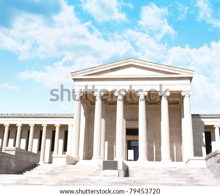 A city courthouse law building with pillar columns and stairs. Bright clouds are in the background. Can represent law, justice or legislation. - stock photo