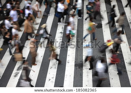 A city cross walk is littered with pedestrians. - stock photo