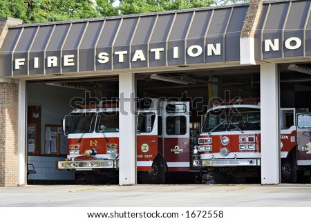 A city fire station - doors open and trucks waiting.