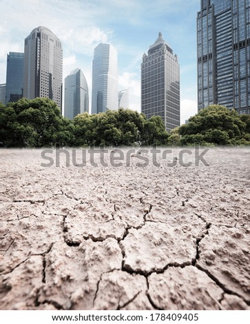 A city looks over a cracked earth landscape