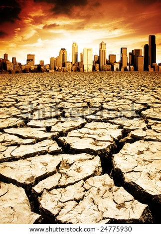 A city looks over a desolate cracked earth landscape - stock photo