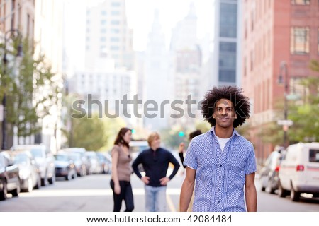 A city setting with a group of friends, a happy African American in the foreground - stock photo