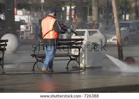 A city worker steam-cleans the sidewalk.