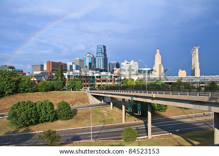 A cityscape view of the downtown Kansas City, Missouri area with a rainbow over the city.  Kansas City borders major rivers and is a major city in the Great Plains. - stock photo