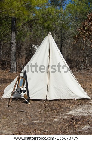 A Civil War era tent and encampment with equipment stacked outside.