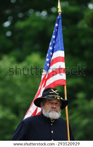 A Civil War re-enactor in a Union uniform marches with an American flag during the Amherst, New Hampshire, Fourth of July parade on July 4, 2015.  - stock photo
