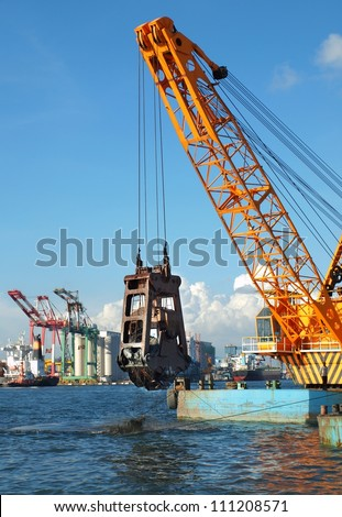 A clamshell dredger mounted on a barge in Kaohsiung port - stock photo