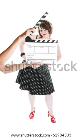 A clapper board being held up in front of a young actress dressed in pinup fashion.  Shot on white background.  Focus on actress. - stock photo