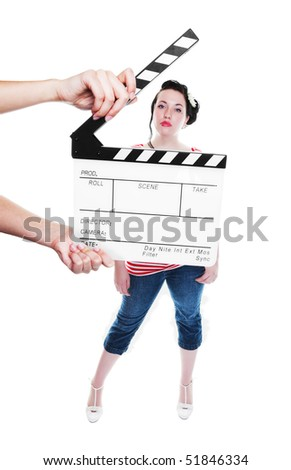 A clapper board being held up in front of a young actress dressed in rockabilly fashion.  Shot on white background.  Focus on clapper board. - stock photo