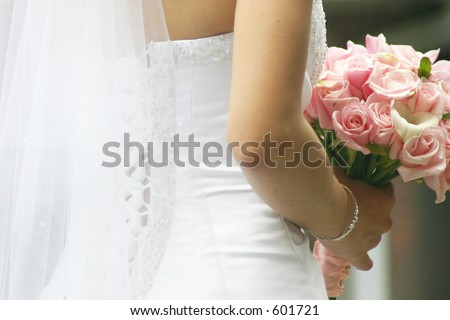 a classic bride poses with pink flowers - stock photo