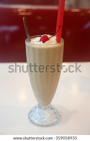 A classic Chocolate Milkshake with Whipped Cream and a Cherry, in a Glass Milkshake glass with a red straw and silver spoon. - stock photo