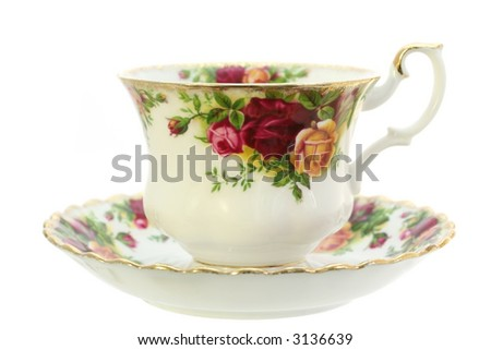 A classic gold-rimmed floral china teacup and saucer.  Isolated on white. - stock photo