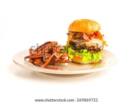 A classic hamburger with cheese, tomatoes. lettuce and crispy fried bacon in between two sesame seed buns and deep fried sweet potato strips on the side of a round plate.  - stock photo