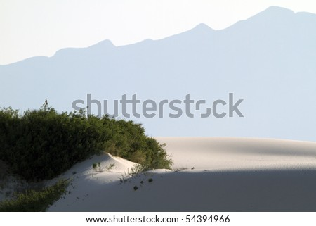 A classic landscape of sand dune, grass, and mountain at White Sands National Monument - stock photo