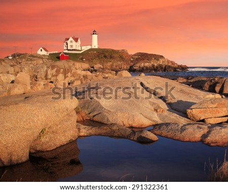 A Classic Lighthouse, Sunset Skies At The Nubble Light, A Pastoral New England Seascape, Cape Neddick, Maine, USA - stock photo