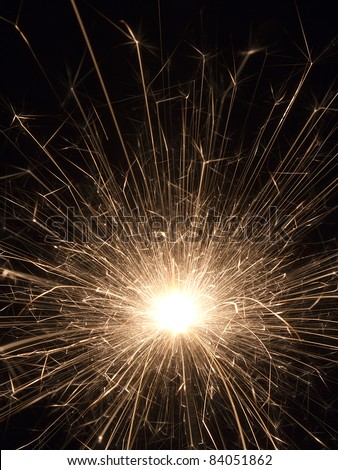 A classic sparkler firework emits a shower of yellow-gold sparks illuminating the darkness. - stock photo