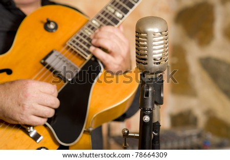 A classic steel guitar and a vintage microphone - stock photo