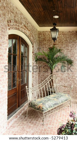 A classic upscale front porch sitting area, ready to relax on. - stock photo