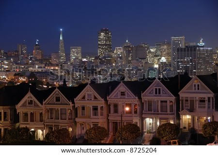 """A classic view of the """"Postcard Row"""" Victorian Houses and downtown San Francisco viewed from Alamo Square park early evening - stock photo"""