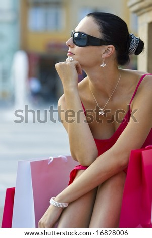 A classically beautiful Mediterranean woman sitting and thinking surrounded by full shopping bags - stock photo