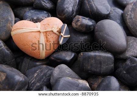 A clay heart on black gravel