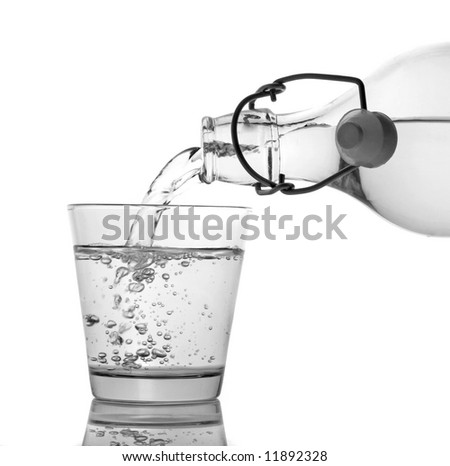 A clean glass of water being served from a bottle isolated on white - stock photo