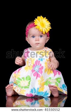 A clean image of a cute baby on black.  The image is isolated with part of the babies reflection.  The adorable baby girl is wearing a yellow flower on her pink head band.