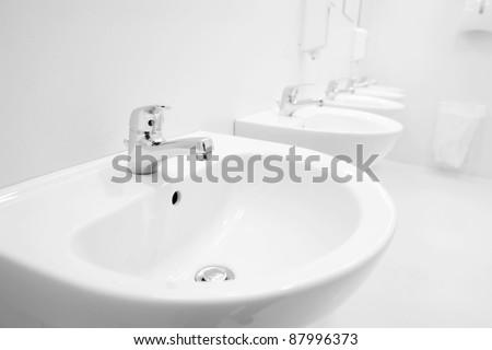a clean new public toilet room empty - stock photo