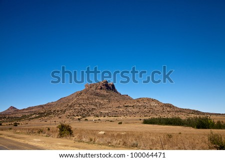 A clear blue sky above a desolate mountain landscape - stock photo
