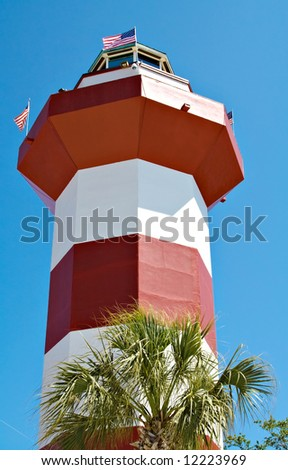 A clear blue sky features the Harbour Town Lighthouse - famous landmark in Hilton Head, SC, USA - stock photo