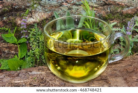 A clear cup of herbal tea in front of different healing herbs used in naturopathic medicine.