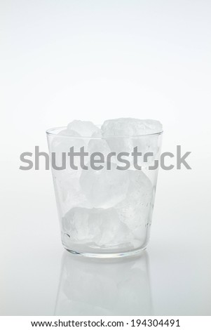 A clear glass cup with pieces of ice inside. - stock photo