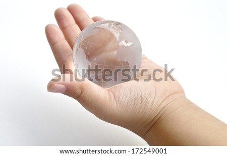 A clear glass globe on a hand, the power to control the world, heal the world, safe the earth, world in hand.