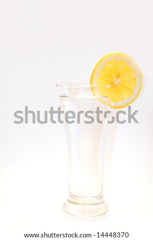 A clear glass of water with a slice of lemon on the rim on a white background.  Space for copy. - stock photo