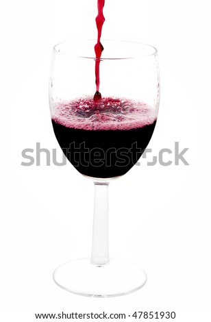 A clear glass with red wine pouring from the top of the picture