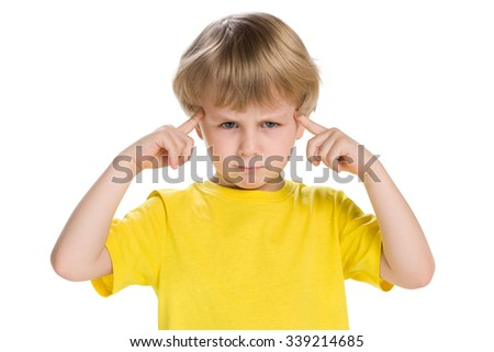 A clever little boy in a yellow shirt stands on the white background - stock photo