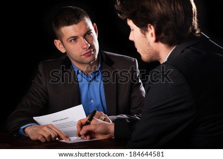 A client signing a loan agreement with his lawyer - stock photo