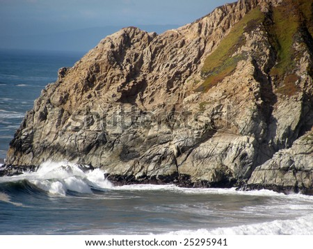 A cliff enclosing a small  bay on the Pacific coast of northern California.